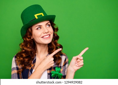 Close up photo of she her lady beautiful brunette fingers show look to empty space novelty wearing casual checkered plaid shirt leprechaun headwear isolated on green vivid vibrant background
