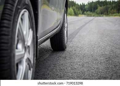A close up photo of a side of a car with two wheels seen and a burned rubber tire track on an asphalt road.