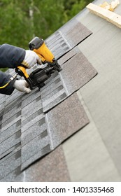 Close up photo of skilled roofer worker in uniform work wear using air or pneumatic nail gun and installing asphalt or bitumen shingle on top of the new roof under construction residential building