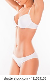 Close up photo of slim woman's body in white lingerie