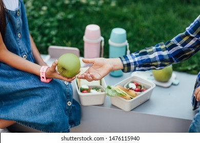 Close up photo, small friends have a picnic, apple on hands, lunch boxes with healthy food and child  with smartwatches. Lifestyle.