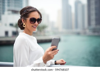 Close up photo of a smiling businesswoman using a mobile phone in the city next to the river.