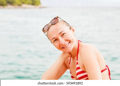 Close up photo of smiling young woman in swimsuit