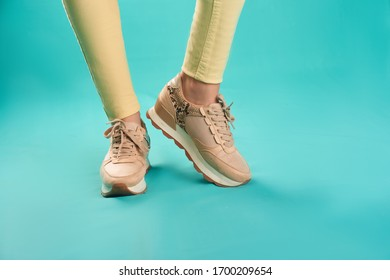 Close up photo of sneakers and yellow skinny jeans against an aqua background in a studio.