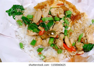 Close up photo of stir fried chicken with holy basil served with crispy fried egg in unwrapped paper, famous Thai street food cuisine