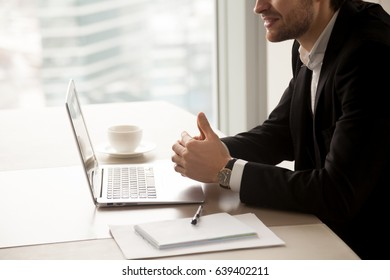 Close up photo of successful businessman sitting at desk with laptop and conducts negotiations. Male entrepreneur communicate with partners in office. Financial consulting, small business assistance