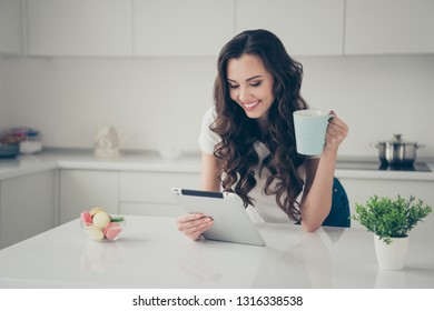 Close up photo sweet beautiful brunette she her lady homey indoors housewife watch e-reader hold beverage read reader glad wearing domestic home apparel clothes outfit comfy table kitchen