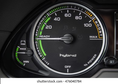 Close up photo of a tachometer of a modern hybrid car. Battery indicator.