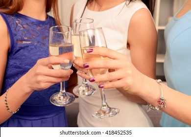 Close up photo of three hands raising glasses with shampagne in a toast