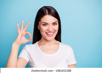 Close up photo of toothy smiling cute pretty sweet woman showing you ok sign of victory while isolated with blue background