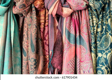 Close up photo of turquoise and pink pashmina scarves hanging up