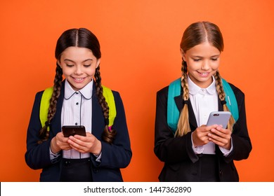 Close up photo two beautiful people she her little ladies funny hands arms telephone reader instagram followers wear formalwear shirt blazer skirt school form bag isolated bright orange background
