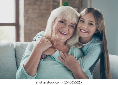 Close up photo of two best friends people cute aged grandma small grandchild girl sitting comfortable sofa hugging piggyback spending weekend together house indoors