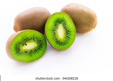 Close up photo of two cut-in-half slices of kiwi, with two whole kiwis behind. The background is isolated.