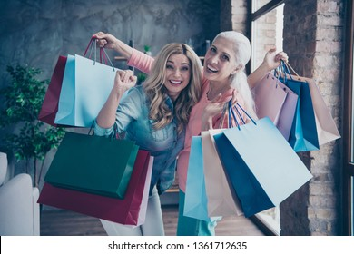 Close up photo two funny beautiful people she her ladies granny granddaughter leaving showroom many clothes outfit new collection buy buyer gifts presents couch divan sofa house indoors