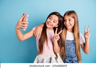 Close up photo two little she her blond brunette girls long pretty hair telephone make take selfies for mom mommy show v-sign wearing casual jeans denim t-shirts isolated blue bright background