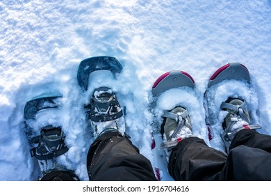 Close up photo of two pairs of snow shoes blue and rose magenta worn on winter boots and shoes, fluffy fresh white snow, much copy space at top side of photo