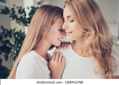 Close up photo of two people pretty mum mommy and teen daughter holding each other hands arms inspired eyes closed lovely wear white t-shirts denim jeans in bright light place flat indoors