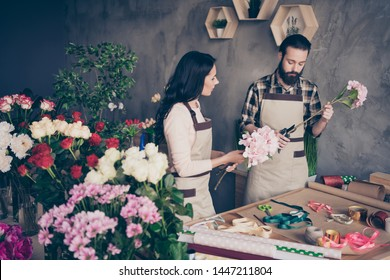 Close up photo two people she her lady watch attentive masterclass lesson him his he guy teach student take care check trimming stems prepare bunch fresh flowers owner small flower shop room indoors