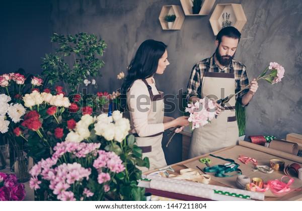 2人の写真の接写は女性が注意深く見守る名人クラスのレッスンを受け、男性が教える生徒が注意深く調べる整髪用のステムを用意し、室内で花屋の小さな花屋を一束作る