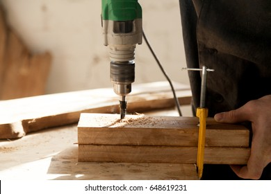 Close up photo of two pieces of dry wood fastened clamp at workbench and drilled with electric drill. Joiner working in carpentry workshop. Professional tools and instrument for woodworking concept