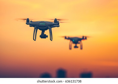 Close up photo of two Professional Remote Control Air Drones with action cameras flying in dramatic sunset sky. Modern technologies. Travel, hobby, inspiration. Pastel orange toning. Kiev, Ukraine