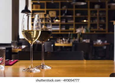 Close up photo of two wine glasses on the table with blurred background and copy space area for a text. Drinks Restaurant background.