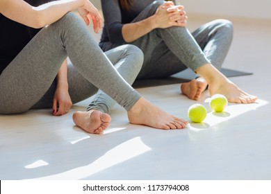 Close up photo of two women's legs - self-massage technique applying tennis balls for legs, back, neck and shoulder pain relief.