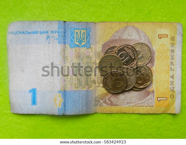 Close up photo of ukrainian coins in nominal value of ten cents lie on one hryvnia with a green background