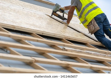 Close up photo of unrecognizible mature builder in protective uniform wear standing on rooftop of new modern building construction. Man holding pneumatic nail gun in hands and fixing roof cover