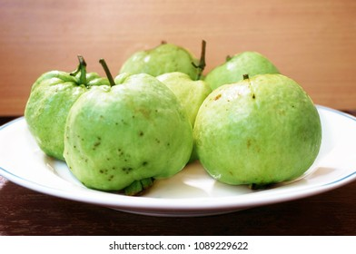 Close up of photo of very fresh green common guava (Psidium guajava) on white plate of wooden background