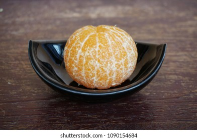 Close up of photo of very fresh orange on black blow on wooden background