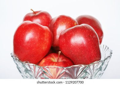 Close up of photo of very fresh red apples on crystal bowl isolated on white background