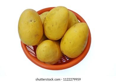 Close up of photo of very fresh ripe mangoes on orange basket isolated on white background