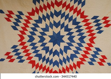 Close up photo of a vintage American patchwork quilt in red, white and blue, Lone Star design