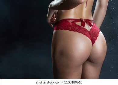 Close Up photo of wet hot and sweaty butt of tanned athletic blonde girl wearing red panties in scenic smoke and fog under falling water drops of rain on black. Healthy smooth skin. Copy space.