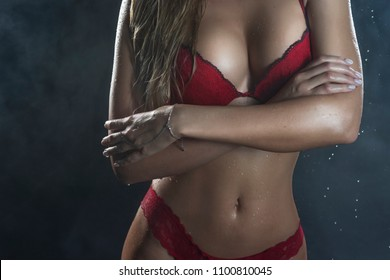 Close Up photo of wet hot and sweaty sensual big tits of tanned athletic blonde girl wearing red bra under falling water drops of rain on black. Healthy smooth skin. Copy space. Advertising design.