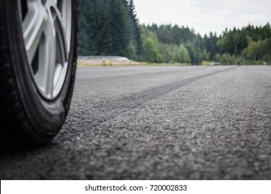 A close up photo of a wheel of a car with a burned rubber tire track on an asphalt road. Focus is on a dark tire trace.