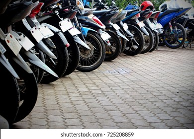 Close up photo of the wheels of motorbikes aligned in a curve in the parking lot.