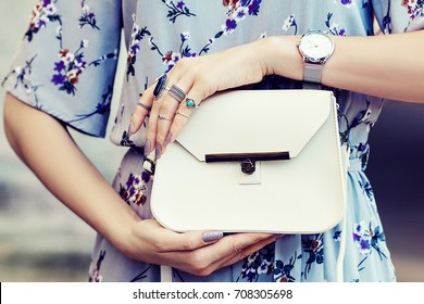 Close up photo of white leather bag in hands of fashionable woman posing in street. Model wearing silvery wrist watch, a lot of rings. Elegant outfit. Female fashion concept