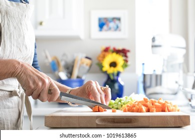 Close up photo of a woman chopping vegetables on a cutting board in a white kitchen with blue accents.