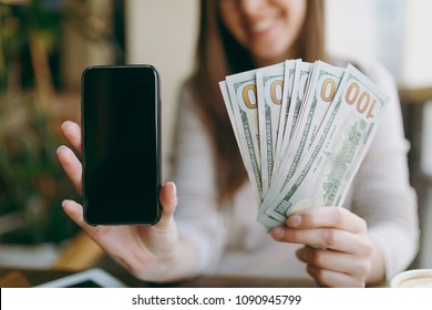 Close up photo of woman in coffee shop at table with bundle of dollars, cash money, mobile phone with blank empty screen to copy space, relaxing in restaurant during free time. Female rest in cafe
