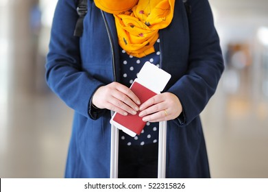 Close up photo of woman holding passport and boarding pass at the airport