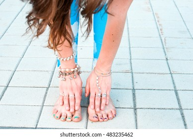 Close up photo of woman legs and hands doing yoga exercises outdoors in the city.Beautiful brunette fit young woman wearing sportswear practicing yoga urban style.Asana,sport,and lifestyle concept