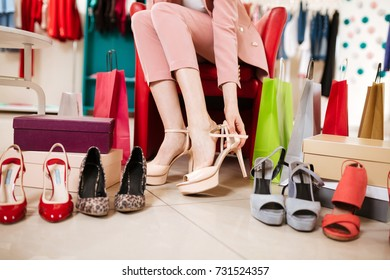 Close up photo of woman legs sitting on chair and measuring different shoes in fashion boutique