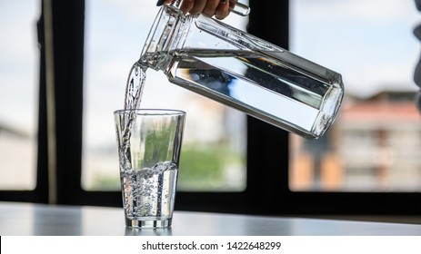 Close up photo of woman pouring drinking water into an empty glass on table.