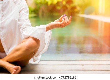 Close up photo of woman practicing yoga and sitting in lotus pose
