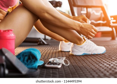 close up photo of woman tying shoelaces of white trainers siting on a mat surrounded by smart phone, earphones, towel and a shaker in the sun lightened gym