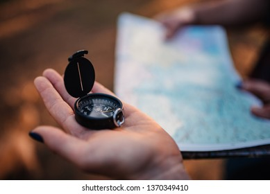 Close up photo of woman using compass and map in the background
