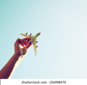 close up photo of woman's hand holding toy airplane against blue sky . image is retro filtered